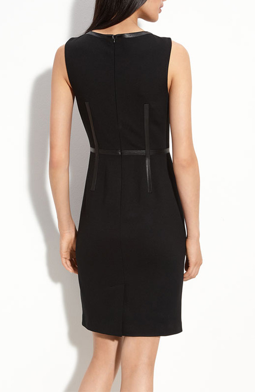 Black dress with leather trims in sleeveless cut with zipper back closure full back view.