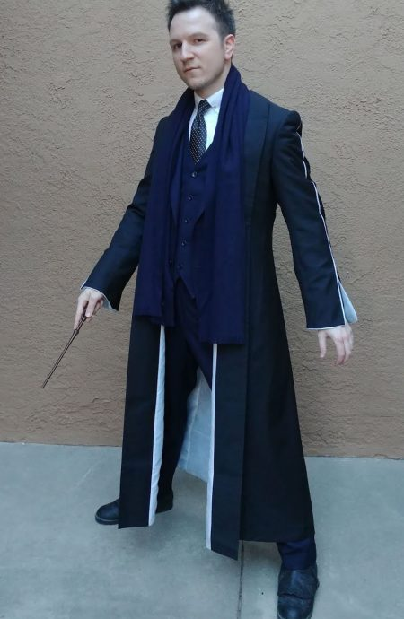 Fantastic Beasts Percival Graves black coat in a mean face posture with wand down.