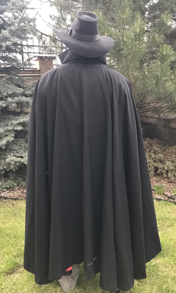 A happy customer in the shadow coat costume with the cape, back view.