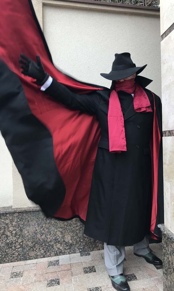 A happy customer in the shadow coat costume with the cape flared, front view.
