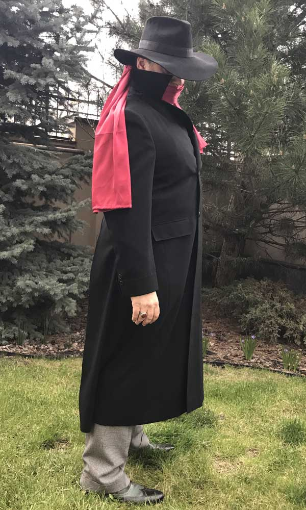 A happy customer in the shadow coat costume without the cape, long coat with the red scarf side view.