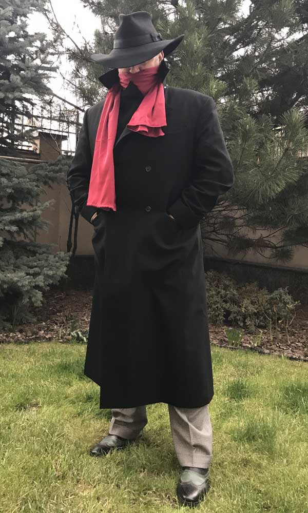 A happy customer in the shadow coat costume without the cape, long coat with the red scarf front view.